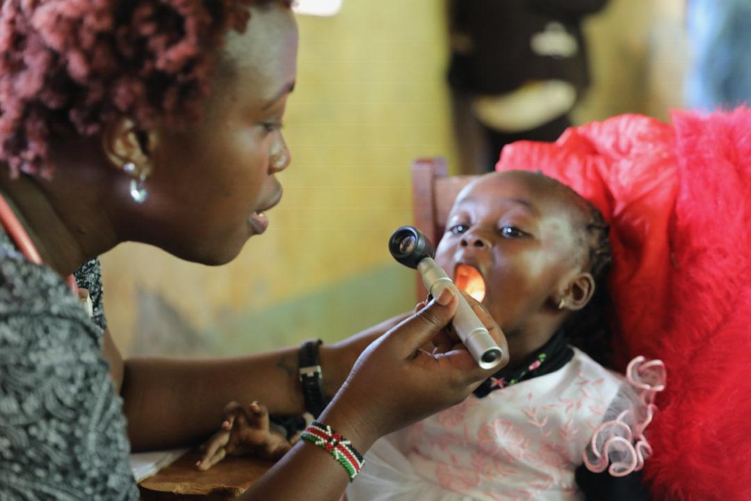Medical volunteer in Kenya works with a baby